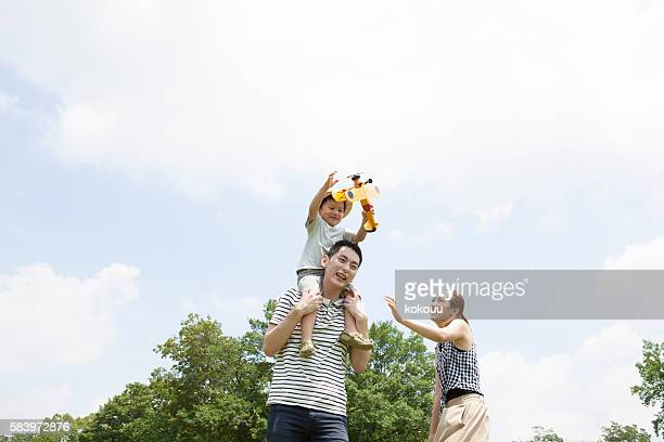 Boy playing with airplane of toys on his father's shoulder