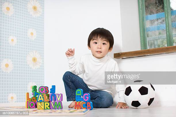 boy (4-5 years) playing with alphabet blocks on floor, portrait - 4 5 years stock pictures, royalty-free photos & images