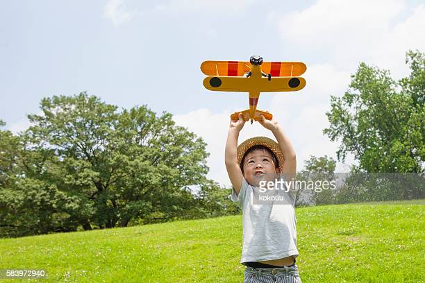 Boy playing with an airplane of toy in the park