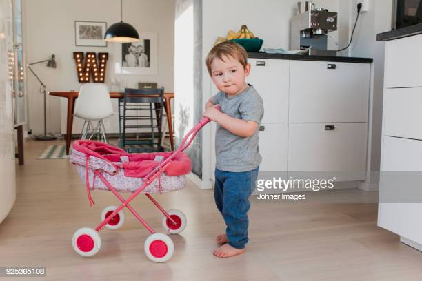 Boy playing with baby carriage in kitchen