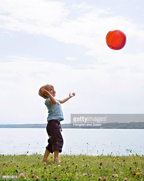 boy playing with ball at lake - nur jungen stock-fotos und bilder