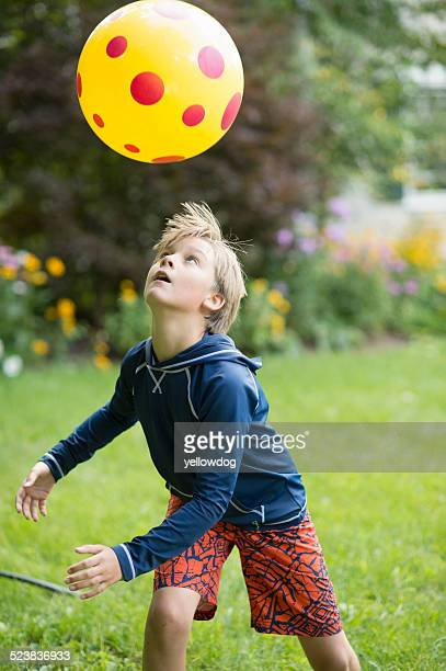 Boy playing with ball game in garden
