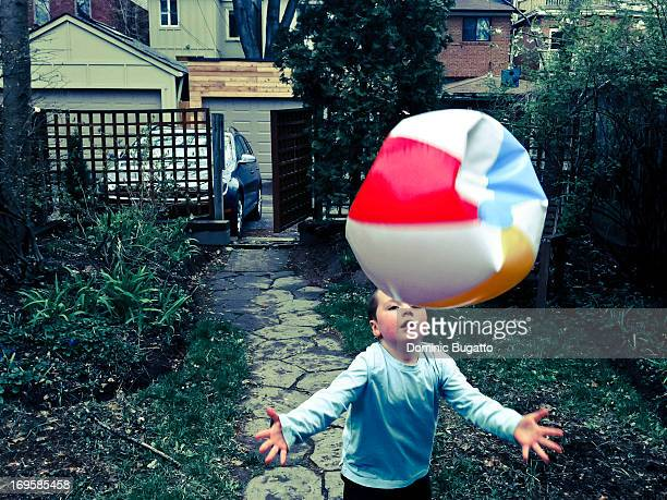 CONTENT] Boy playing with ball in backyard