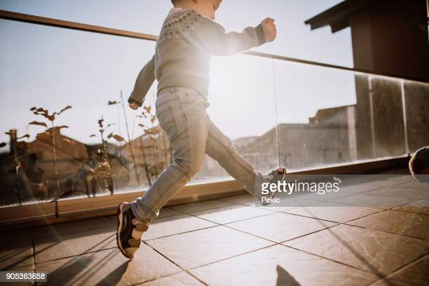 boy playing with ball on balcony - balcony stock pictures, royalty-free photos & images