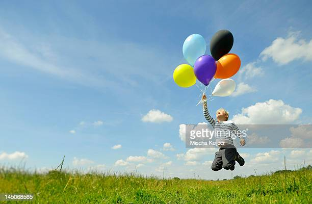 Boy playing with balloons in meadow
