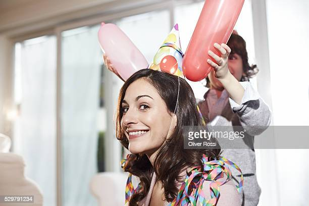 Boy (7-9) playing with balloons on mothers head