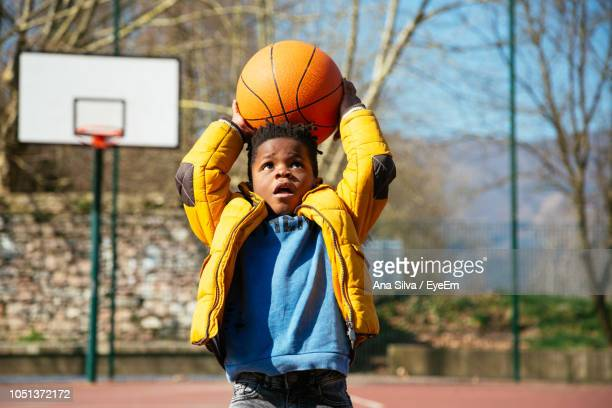Boy Playing With Basketball At Court