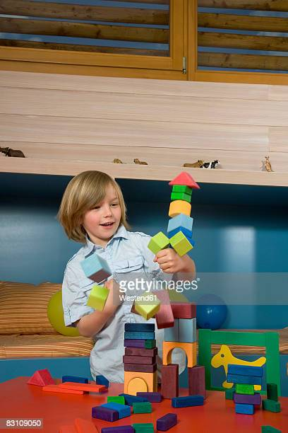 Boy (8-9) playing with building blocks, smiling