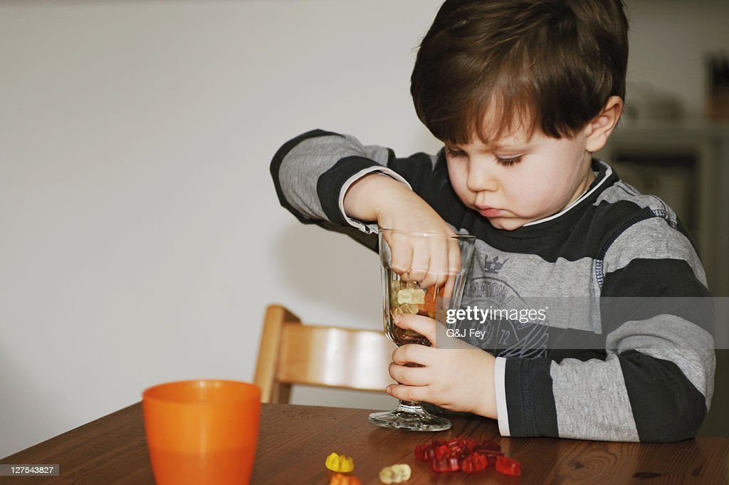 Boy playing with candy at table : Stock Photo