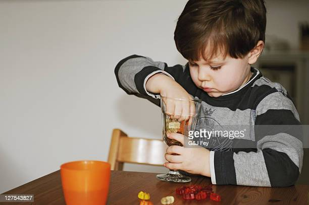 boy playing with candy at table - gummi bears stock photos and pictures