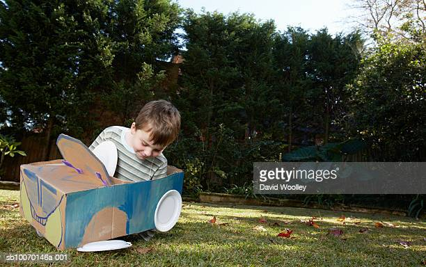 boy (6-7) playing with car made from cardboard box and plates - cardboard box stock pictures, royalty-free photos & images