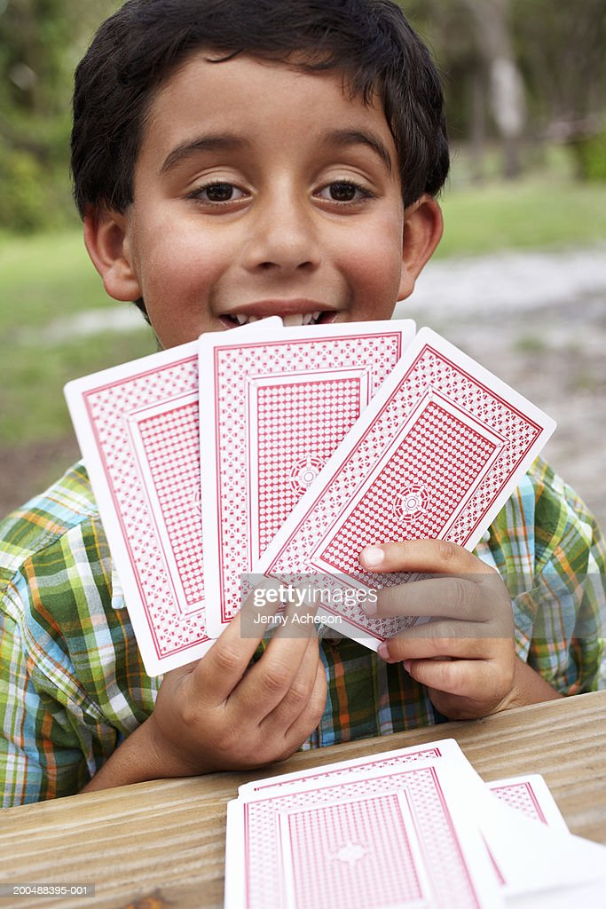 Boy (6-8) playing with cards at garden table, close-up, portrait : Stock Photo