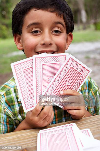 Boy (6-8) playing with cards at garden table, close-up, portrait