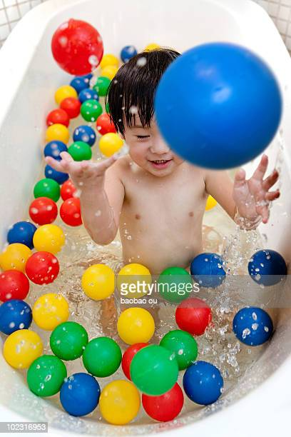 Boy playing with color balls in the bathtub