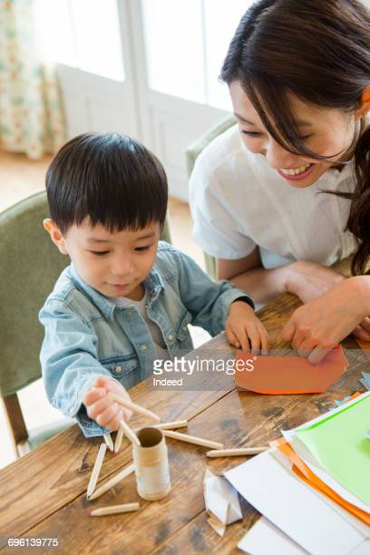 Boy playing with coloring pens next to mother at table
