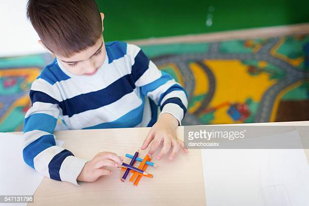 Boy playing with crayons in the class room