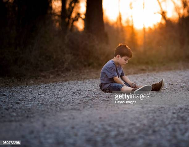 Boy playing with dirt on road during sunset