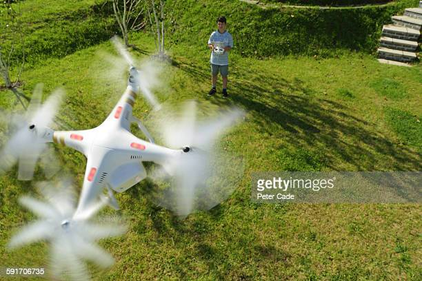 boy playing with drone in garden - drone foto e immagini stock