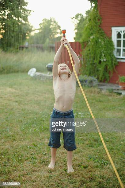 Boy playing with garden hose in garden