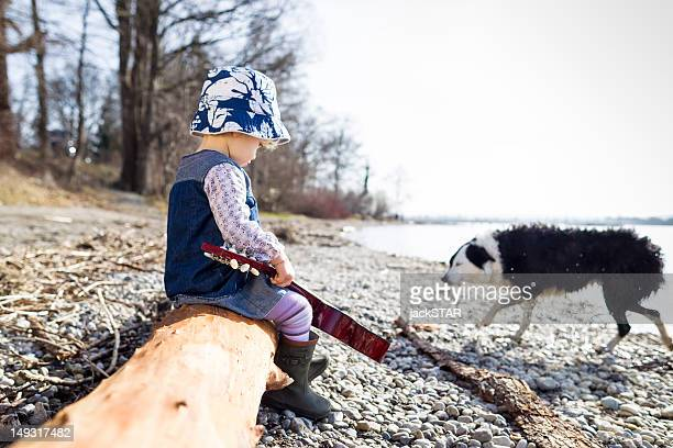 Boy playing with guitar on log