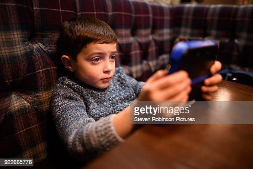 Boy Playing with hand held Games Console 2