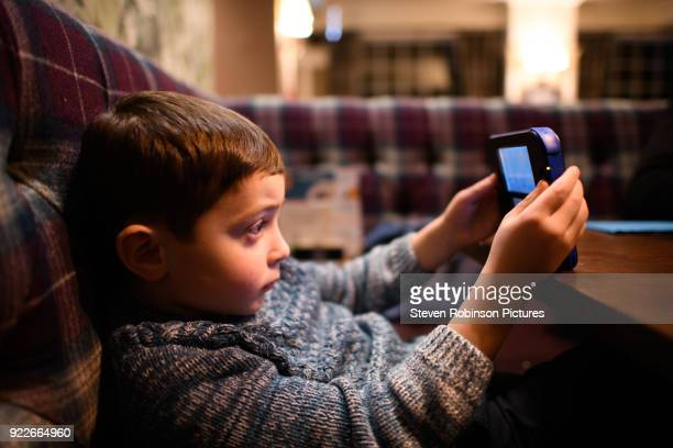 boy playing with hand held games console - video still stock photos and pictures