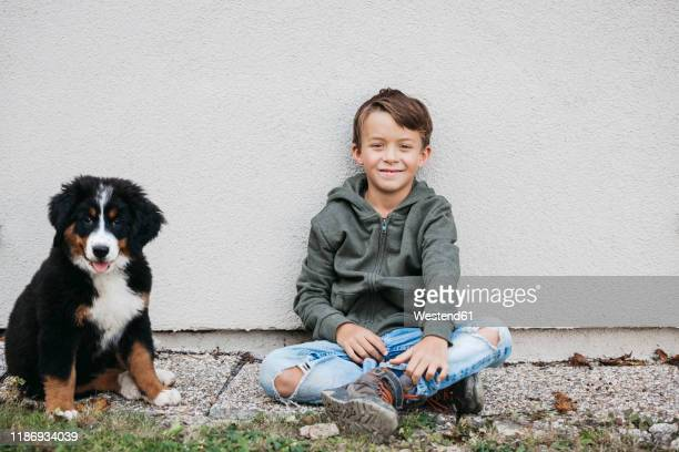 boy playing with his bernese mountain dog in the garden - alleen jongens stockfoto's en -beelden