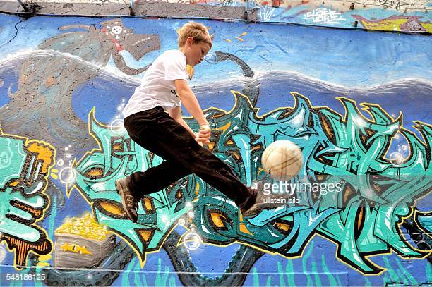 boy playing with his football in front of a graffiti wall