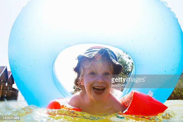 boy playing with inner tube in pool - arm band stock pictures, royalty-free photos & images