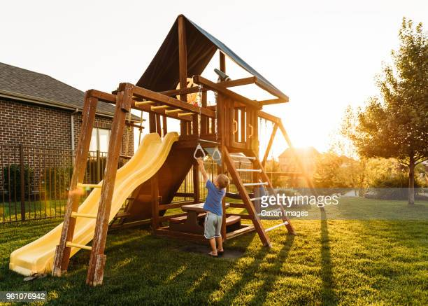 boy playing with jungle gym in backyard during sunset - ジャングルジム ストックフォトと画像