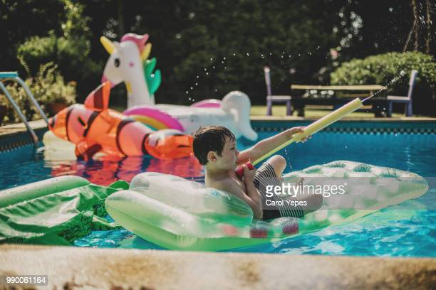 boy playing with matress on pool