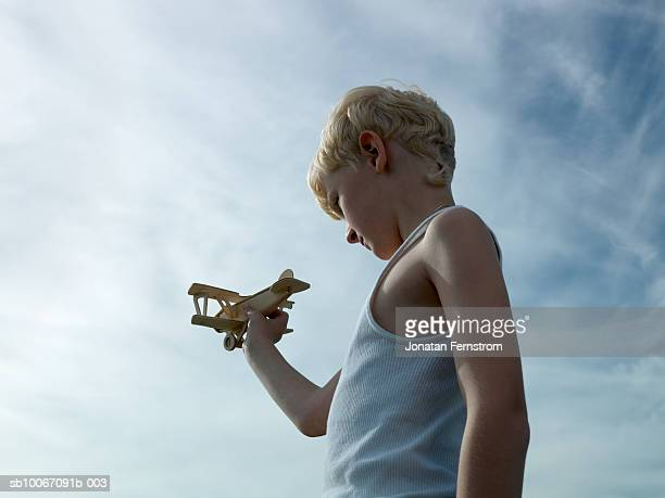 Boy (6-7) playing with model aeroplane, low angle view