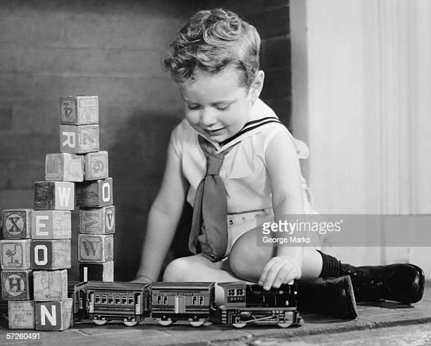 Boy (4-5) playing with model train set on floor, (B&W),