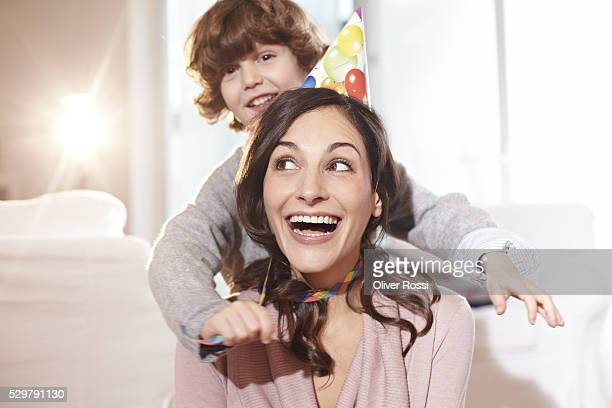 Boy (7-9) playing with mothers party hat in living room