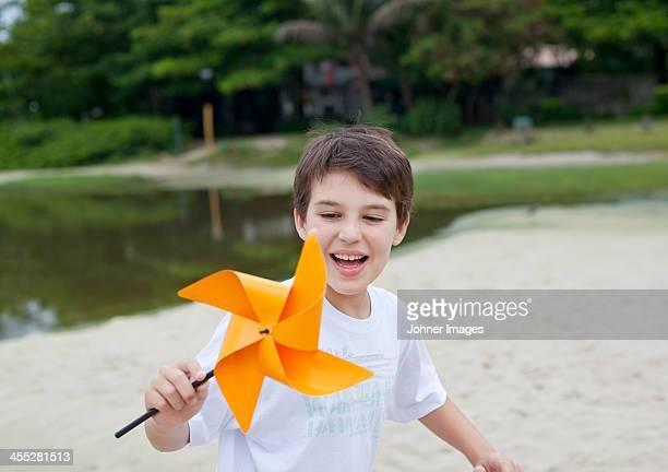 Boy playing with orange pinwheel
