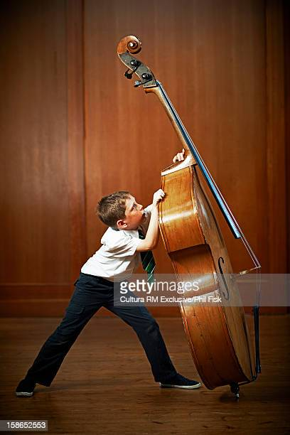 Boy playing with oversized cello