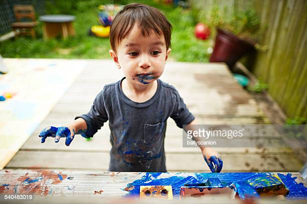Boy Playing With Paint In Garden.