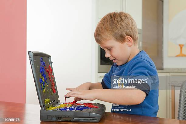 Boy playing with paint on laptop