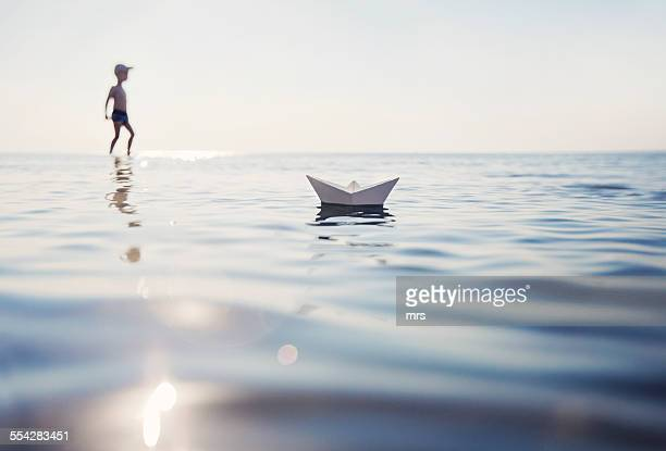 Boy playing with paper boat in the sea