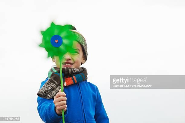 Boy playing with pinwheel outdoors