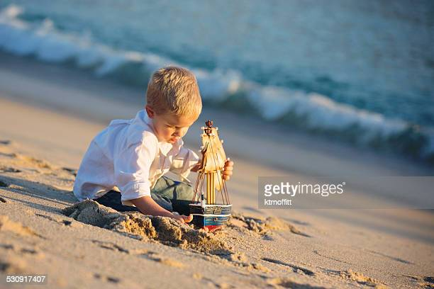 Boy Playing With Pirate Ship At the Beach
