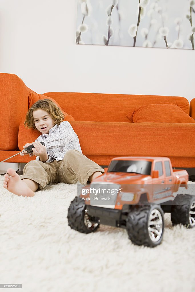 Boy (6-7) playing with remote control car : Stock Photo