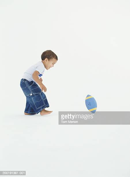 Boy (2-4) playing with rugby ball, side view
