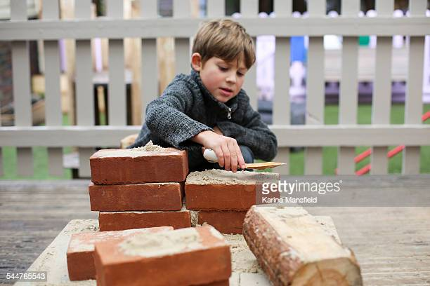 Boy playing with sand and bricks outside