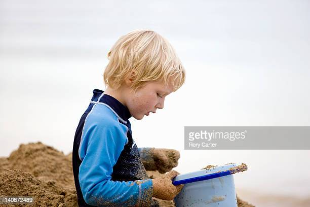 Boy playing with sand on beach