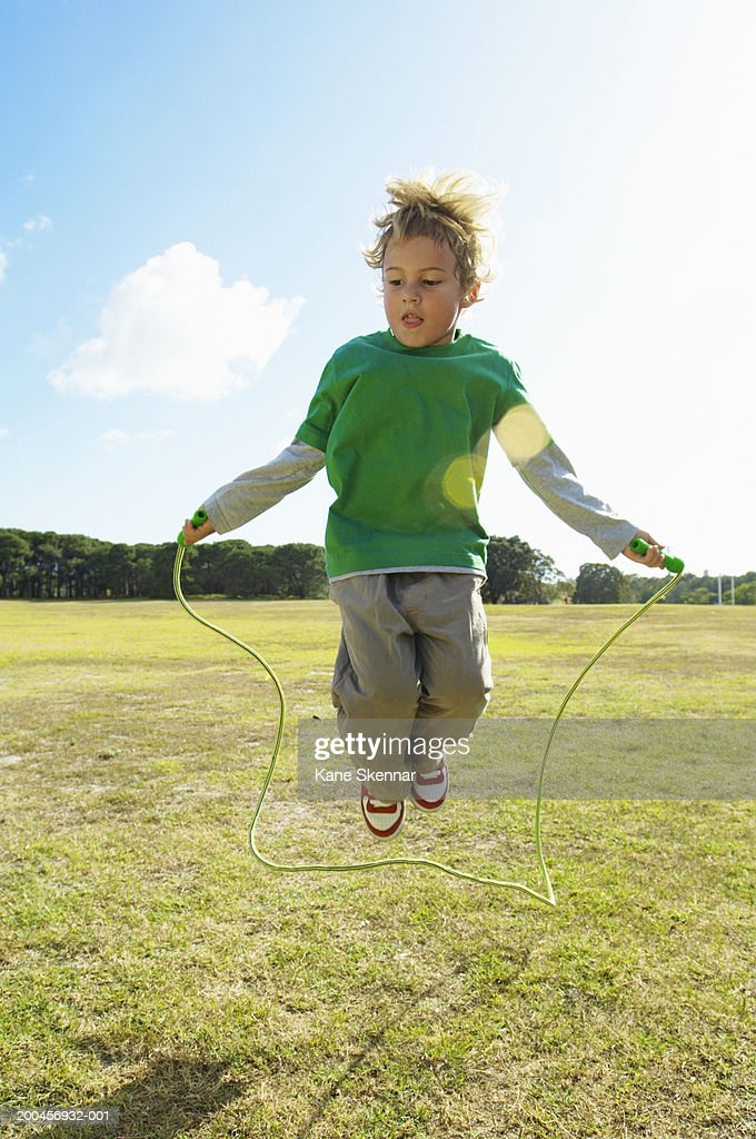Boy Playing With Skipping Rope In Park Jumping Over Rope