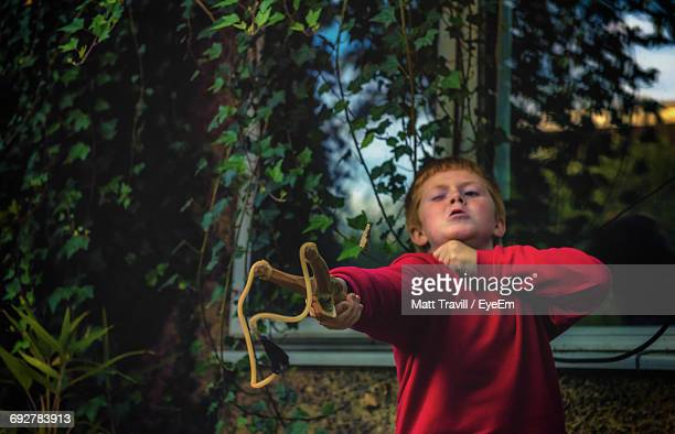 Boy Playing With Slingshot In Yard