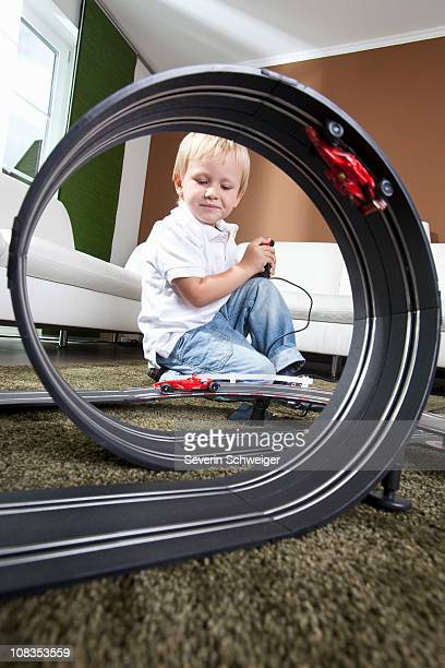 Boy playing with slot car racing track