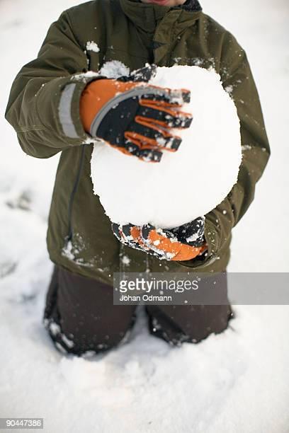 Boy playing with snowballs Gotland Sweden.