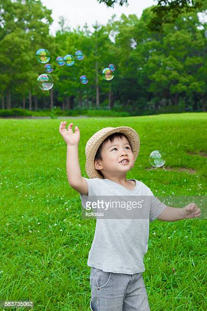 Boy playing with soap bubbles in the park